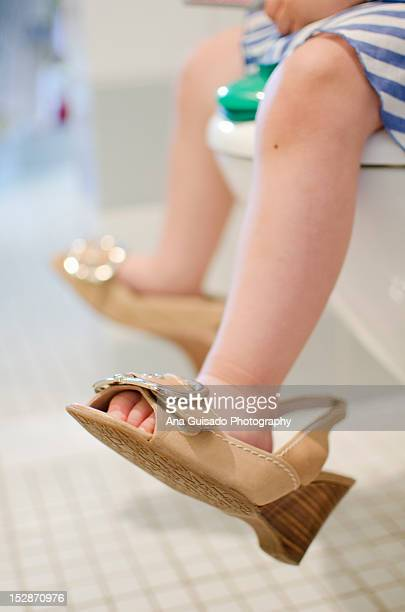 Little girl's legs while sitting on toilet