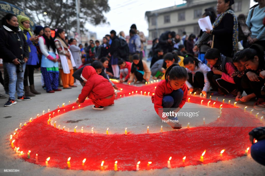 A little girls lit candles around the symbol of RED AIDS during Eve of World AIDS Day celebrated in Kathmandu, Nepal on 1st Dec, 2017. World AIDS Day is celebrated worldwide on December 1st of every year to raise the awareness in the fight against HIV. According to the end of 2014 statistics of National Center for AIDS and STD Control, a total no. of 39,249 estimates affected patients identified in Nepal.