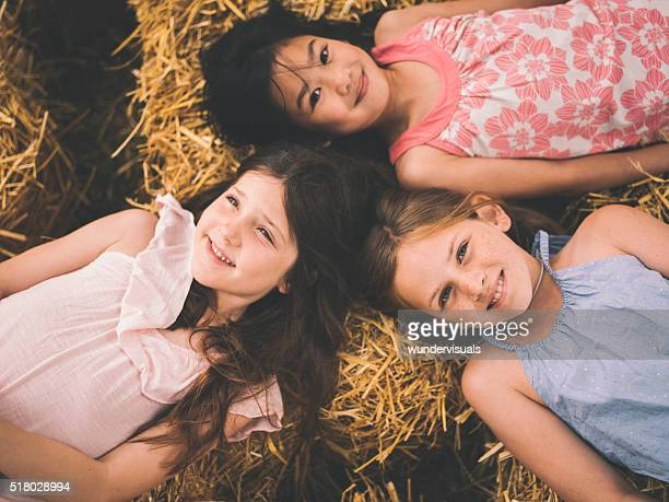 Little girls lying on straw in circle with heads together