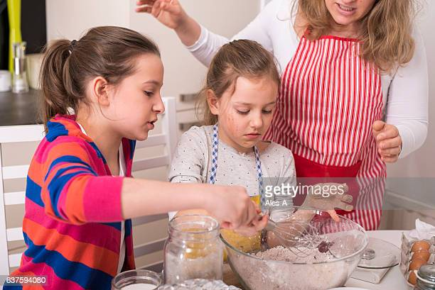 Little girls making muffins with their mom