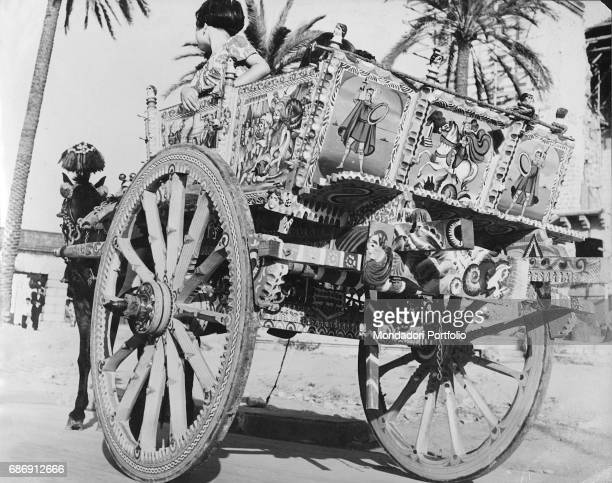 Little girls on a Sicilian cart decorated with battle scenes Sicily 1950s