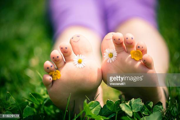 Little girl's painted toes decorated with daisies, Bellis perennis, and buttercups, Ranunculus