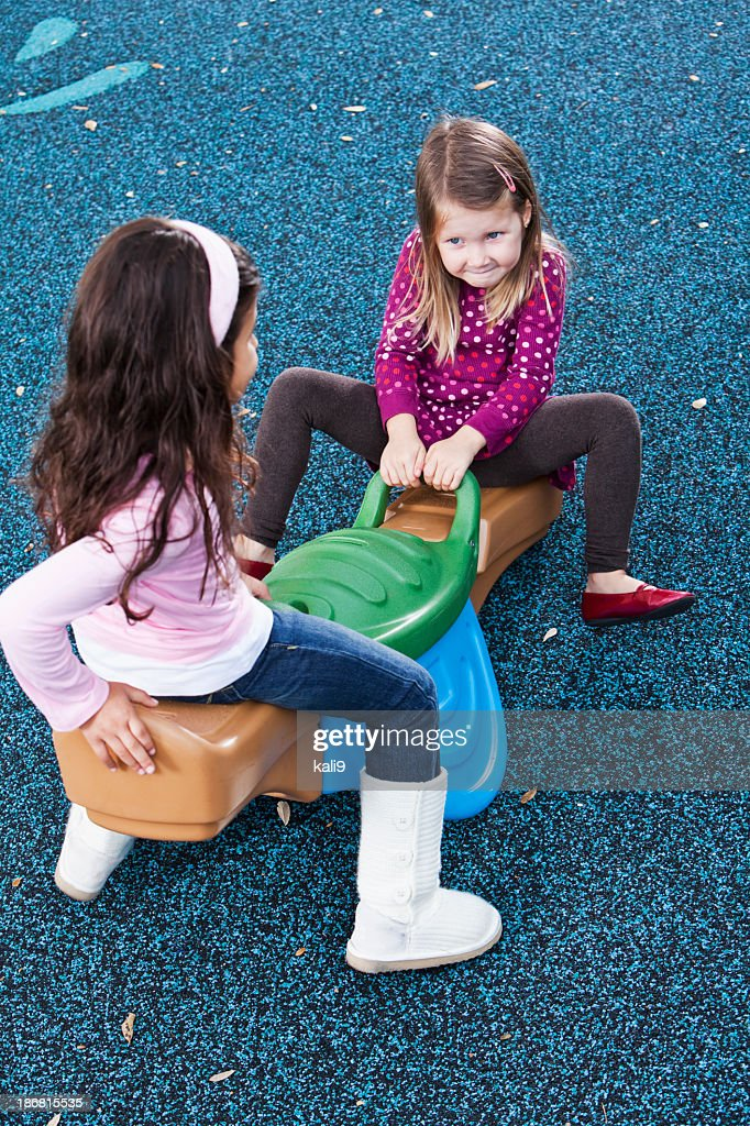 Little girls playing on seesaw