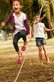 A DSLR picture of two cute little girls skipping rope in a park in Rio de Janeiro, Brazil. The one actualy skipping is having a great time, shouting with joy. They are outdoors and softly lit by the l