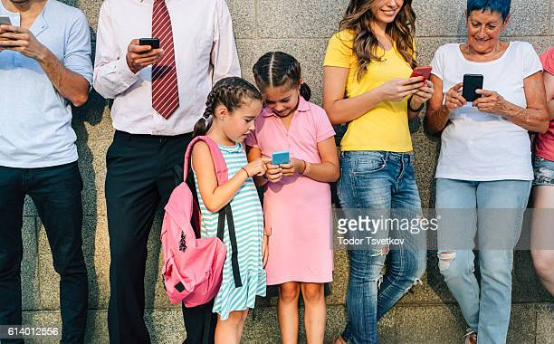 Little girls texting among adults