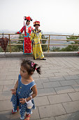 A little girls walks past two Chinese tourists posing for photographs wearing traditional clothing on a promenade above the Forbidden City Beijing...