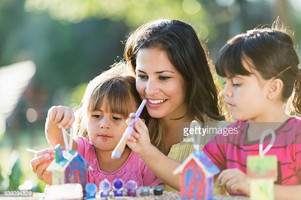 Little girls with mother painting bird houses