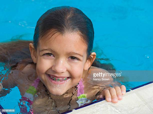 Little girt with braces in pool.