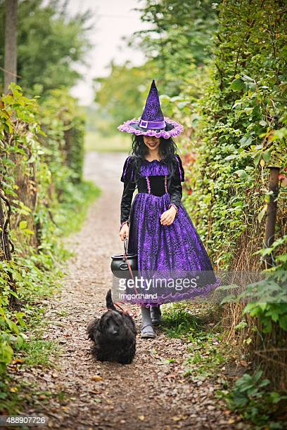 Little halloween witch walking with her dog