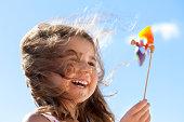 Little happy girl with pinwheel