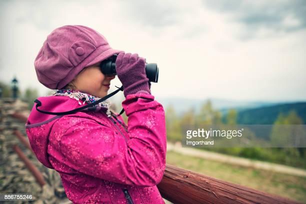 Wanderer-Mädchen mit einem Fernglas betrachten