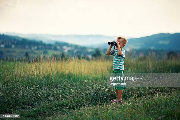 Little hiker looking at view with binoculars