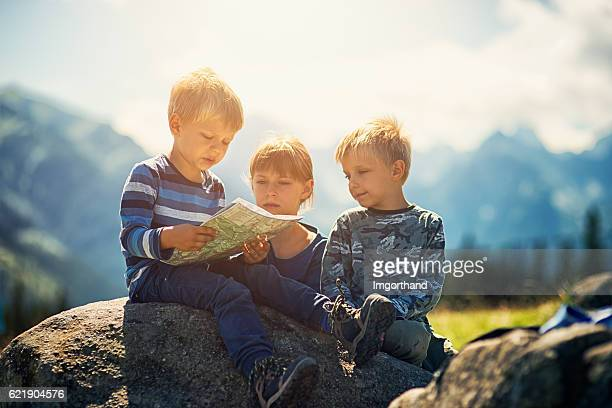 Little hikers checking map in mountains