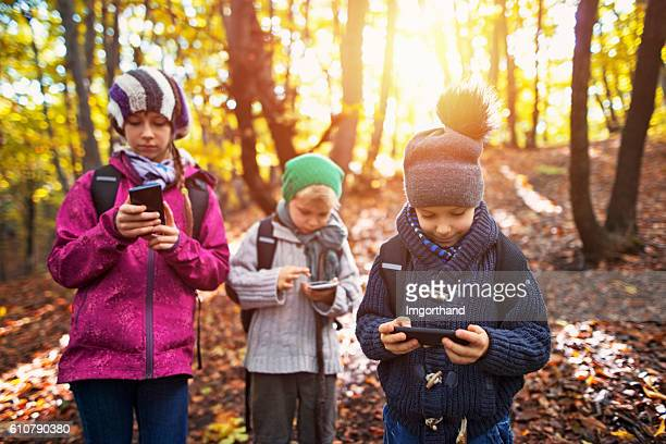 Little hikers in an autumn forest using mobiles