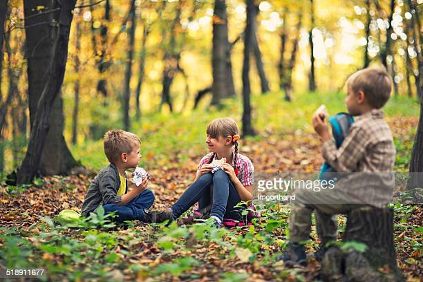 Little hikers resting and eating sandwiches