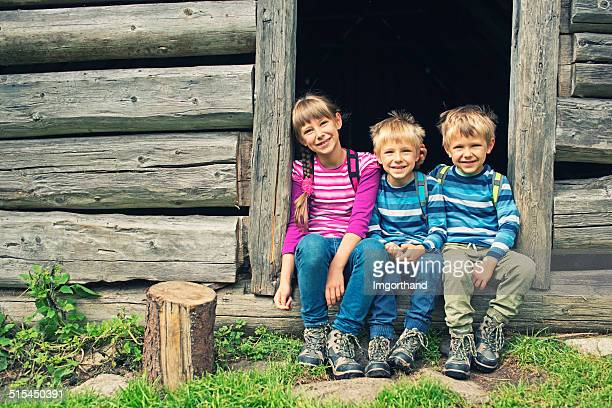 Little hikers resting in front of old wood cabin