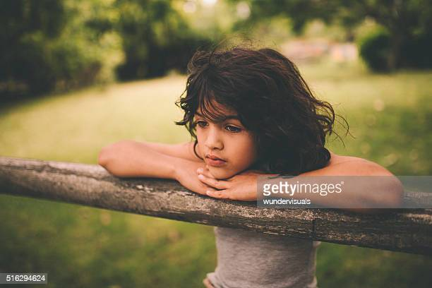 Little hispanic boy leaning on a rustic wooden fence thinking