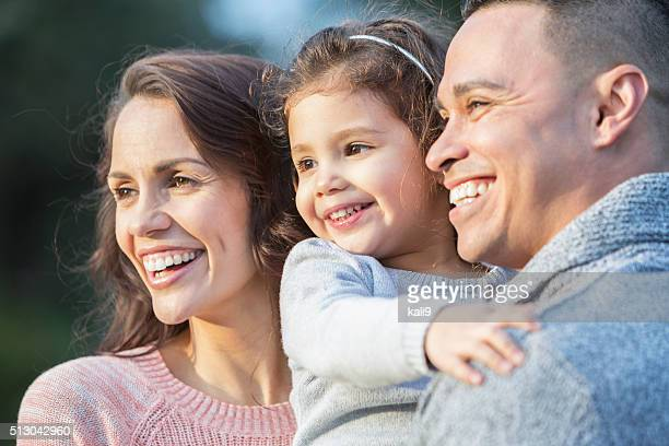 Little Hispanic girl with parents, watching