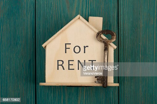 "Little house with text ""For rent"" and key : Stock Photo"