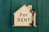"Little house with text ""For rent"" and key on blue wooden background"