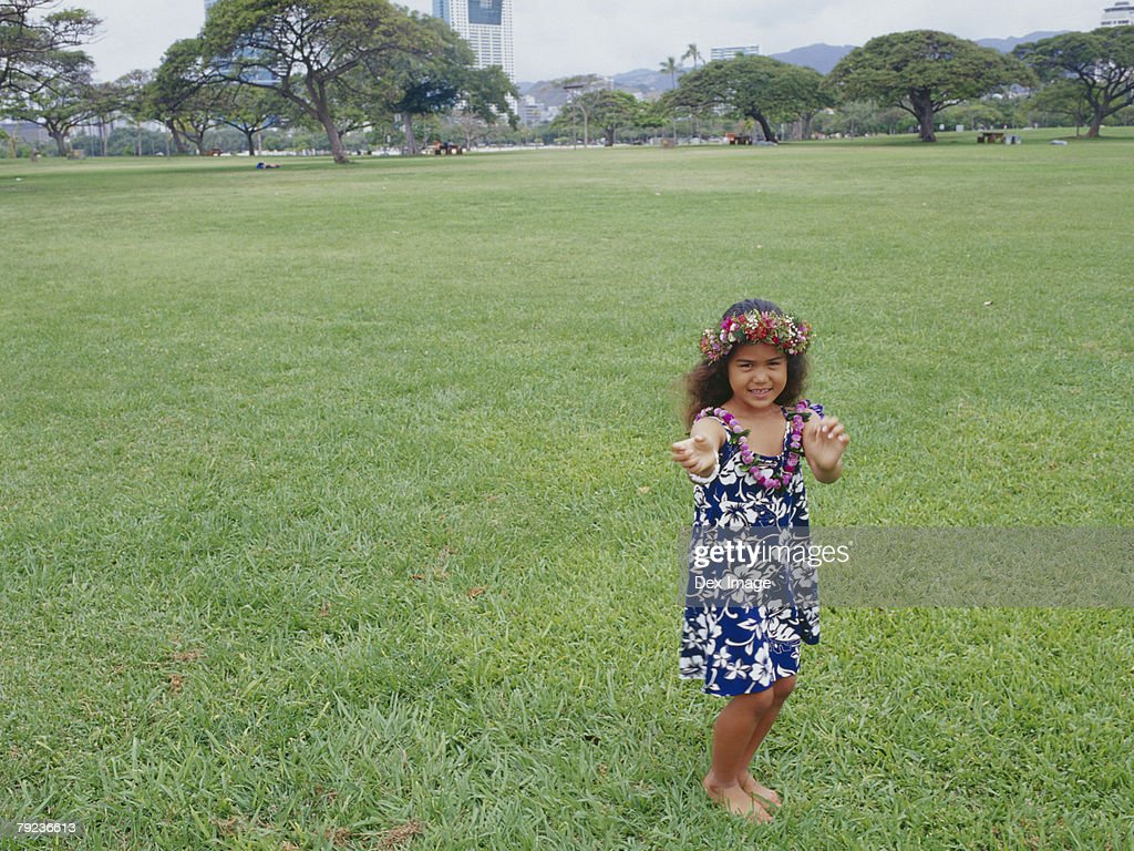 Little hula girl dancing at the field : Stock Photo
