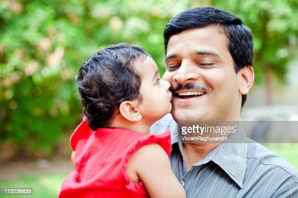 Little Indian girl kissing her father showing affection