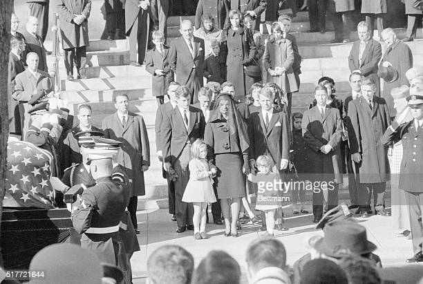 Little John F Kennedy Jr stands by his mother Mrs Jacqueline Kennedy and his sister Caroline as the casket containing the remains of President...