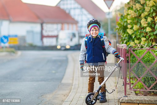 Little kid boy in helmet riding with scooter through city : Stockfoto