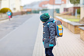 Little kid boy with eye glasses walking from the school. Child on a street. Preschooler wearing warm spring, autumn or winter clothes, glasses and backpack. Happy student or people. Education concept