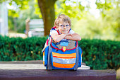 Happy little kid boy with glasses and backpack or satchel on his first day to school or nursery. Child outdoors on warm sunny day, Back to school concept