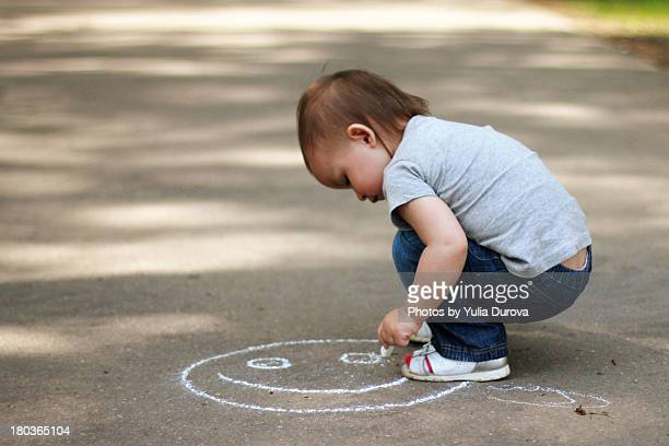 Little kid drawing a smiling face
