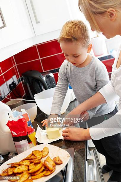 Little kid helping mother cooking in the kitchen