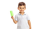 Little kid holding a green popsicle and looking at the camera isolated on white background