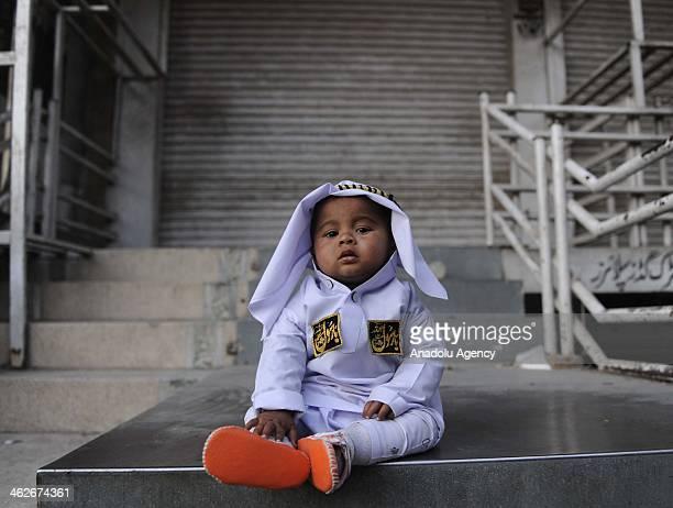 A little kid sits on a sidewalk as Pakistani Muslims attend the Mawlid celebrations marking the birth of Prophet Muhammad in Rawalpindi Pakistan...