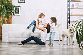 Little kids girls are beautiful and cute with mother and pet dog at home together happy