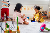 Little kids playing toys in the playroom
