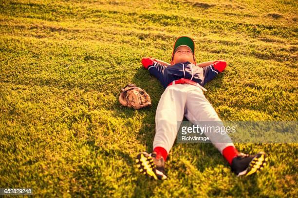 Little League Baseball Boy Relaxes on Field
