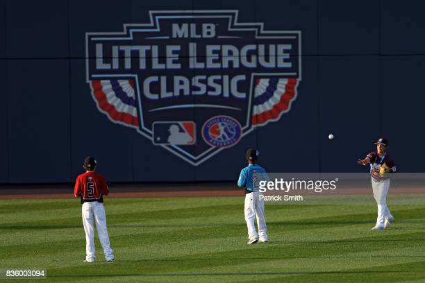 Little League baseball players rally a first pitch from the outfield before the Pittsburgh Pirates play the St Louis Cardinals in the inaugural MLB...