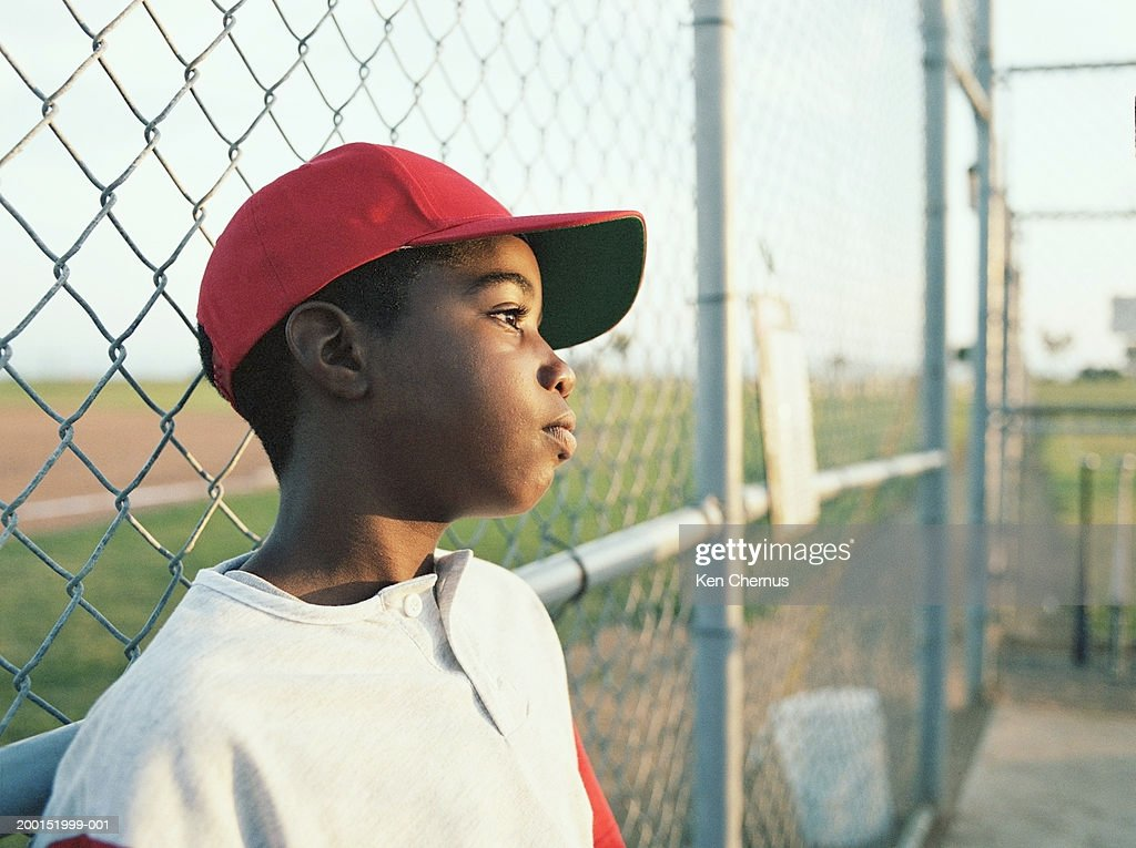 Little league player leaning against fence : Stock Photo
