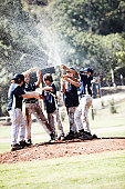 Little league players celebrate with soda.