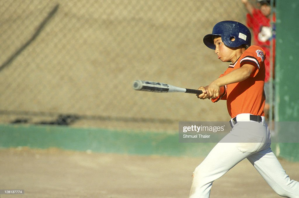 Little leaguer in batting helmet at bat
