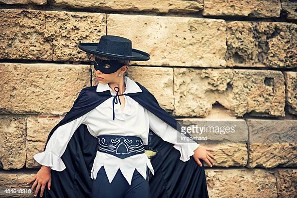 Petite fille de masque du héros sneaking passé vieux mur
