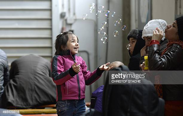 A little migrant girl is delighted by soap bubbles at the first registration hall of the German federal police in the small Bavarian village...