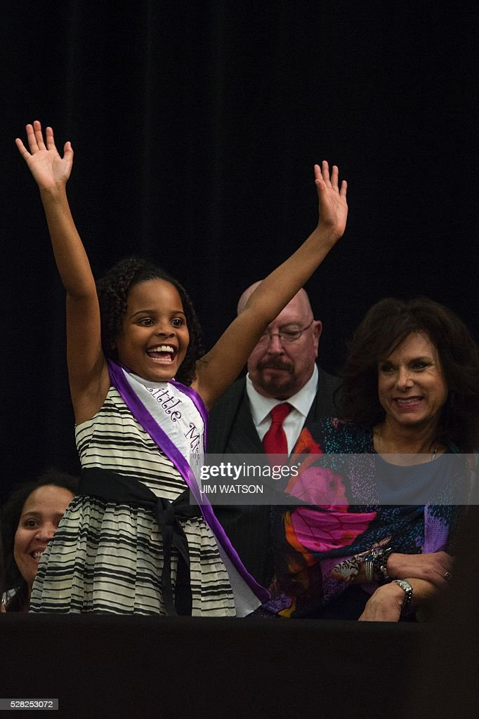 'Little Miss Flint' Mari Copeny, 8, waves during an event at Northwestern High School in Flint, Michigan, May 4, 2016, where US President Barack Obama met with locals for a neighborhood roundtable on the drinking water crisis. Copeny wrote to the president before she traveling 12 hours by bus with more than 200 Flint residents to a congressional hearing on the city's water crisis. / AFP / Jim Watson