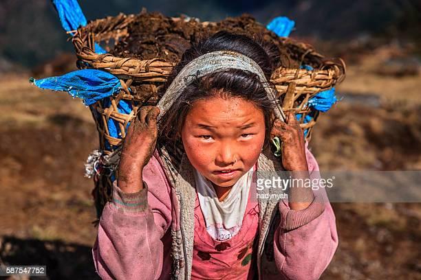 Little Nepali Mädchen tragen etwa 40 kg yak den Kot