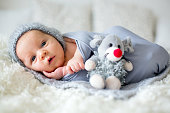 Little newborn baby boy, looking curiously at camera, lay dawn in bed, holding little toy