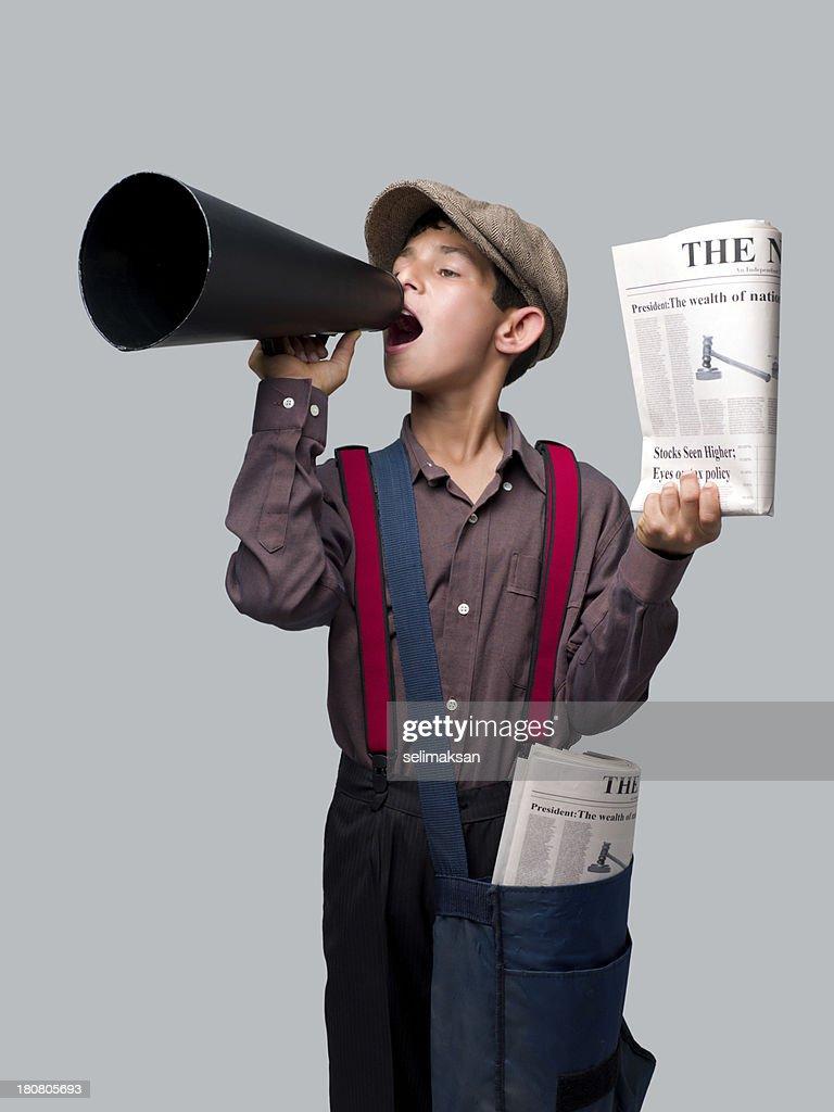 Little Newsboy en tenant des journaux et crier sur Porte-voix à vendre : Photo
