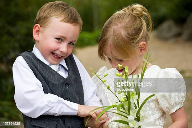 Petit Page garçon tenant mains avec fleur fille à l'extérieur de l'hôtel