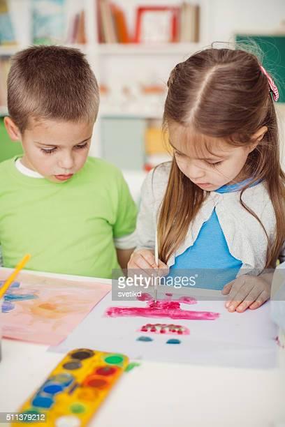 Pintores pequeño de trabajo en la sala de juegos