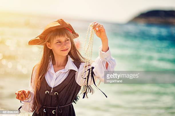 Little pirate captain girl enjoying her treasure